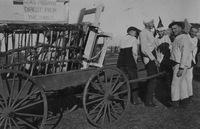 "Freshmen pulling cart in Quad, holding freshmen labelled ""Genus freshmen - direct from the jungle,"" September or October 1920."