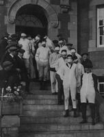 Freshmen, blindfolded, on steps of Athabasca Hall, F.J. Newson at front. September or October 1920.
